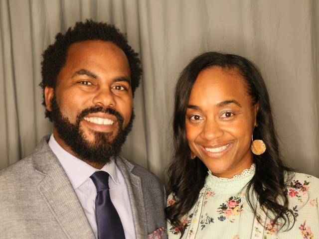 "Faculty Director Maisha T. Winn and Executive Director Lawrence ""Torry"" Winn smiling, next to each other behind a gray curtain background."